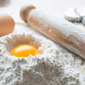 Eggs and flour on table with rolling pin