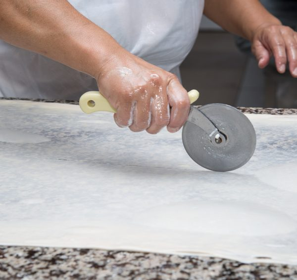 close up of female hands kneading dough and making banitsa - typical bulgarian pastry