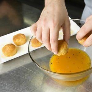 Beautiful cooked pastry dumplings,  being dipped in an orange sweet fruit sorbet.