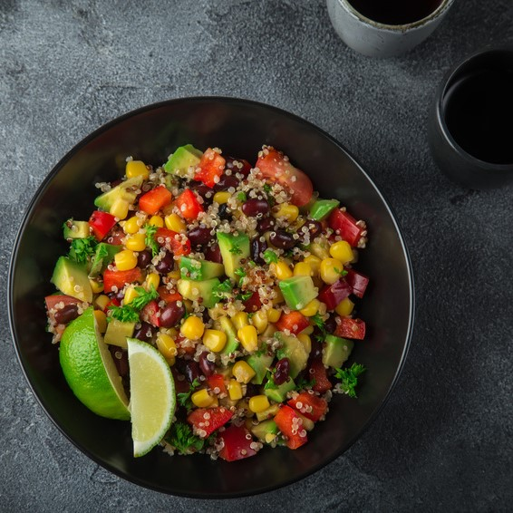 Avocado, quinoa, bean, corn and bell pepper salad . Top view